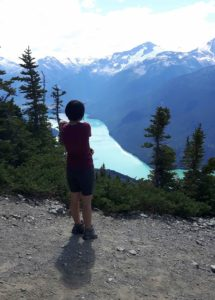 A young Indigenous woman stands on a trail looking out over a mountain range and alpine lake, as part of the Work 2 Live program funded by MEC