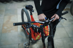 A young person tightens the brakes on a downhill mountain bike for a customer