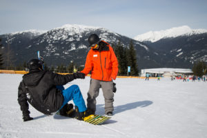 A Whistler Blackcomb snowboard instructor helps a young man stand up on his snowboard