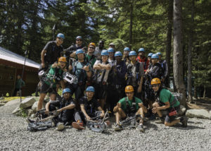 A group of young people pose for a photo after taking part in a ziplining activity in Whistler, BC