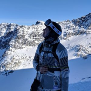 A young First Nations man dressed in snowboard gear looks out over a mountain range