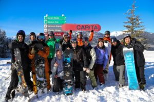 A group of young people in snowboard gear pose for a photograph after a successful day of outdoor adventure
