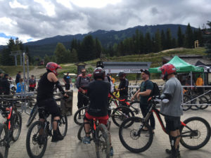 12 young people sit on mountain bikes with a tree-lined mountain slope behind them.