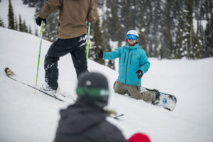 three people in winter clothing are in the snow. One person on skis passes by a snowboarder who has fallen to his knees.