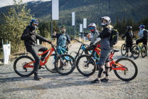 A group of four young people stand with their mountain bikes and smile at the camera