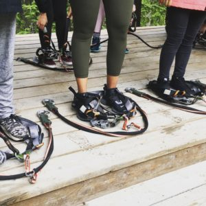 3 pairs of legs stand on a wooden floor with rope-course equipment at their feet as they prepare to put on their gear and do a tree-top adventure course.