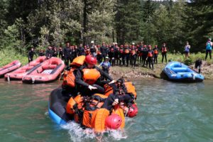 A group of people wearing life jackets on a raft play a wrestling game and try to throw each other into the lake. A crowd cheers behind them
