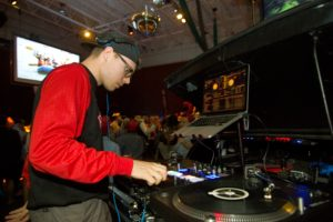DJ Nick Bike spins records for a large crowd of people dancing