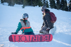 two women in snowboard gear sit and chat on a snow-covered slope.