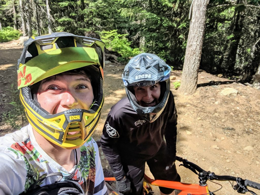 a teen male and adult woman are dressed in biking helmets in the forest. They are happy to be engaging in outdoor recreation