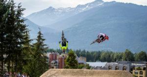 two men performing tricks on mountain bikes.