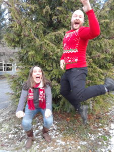 a smiling white woman in cold-weather gear crouches down, while a happy white man in a red Christmas sweater leaps in the air.