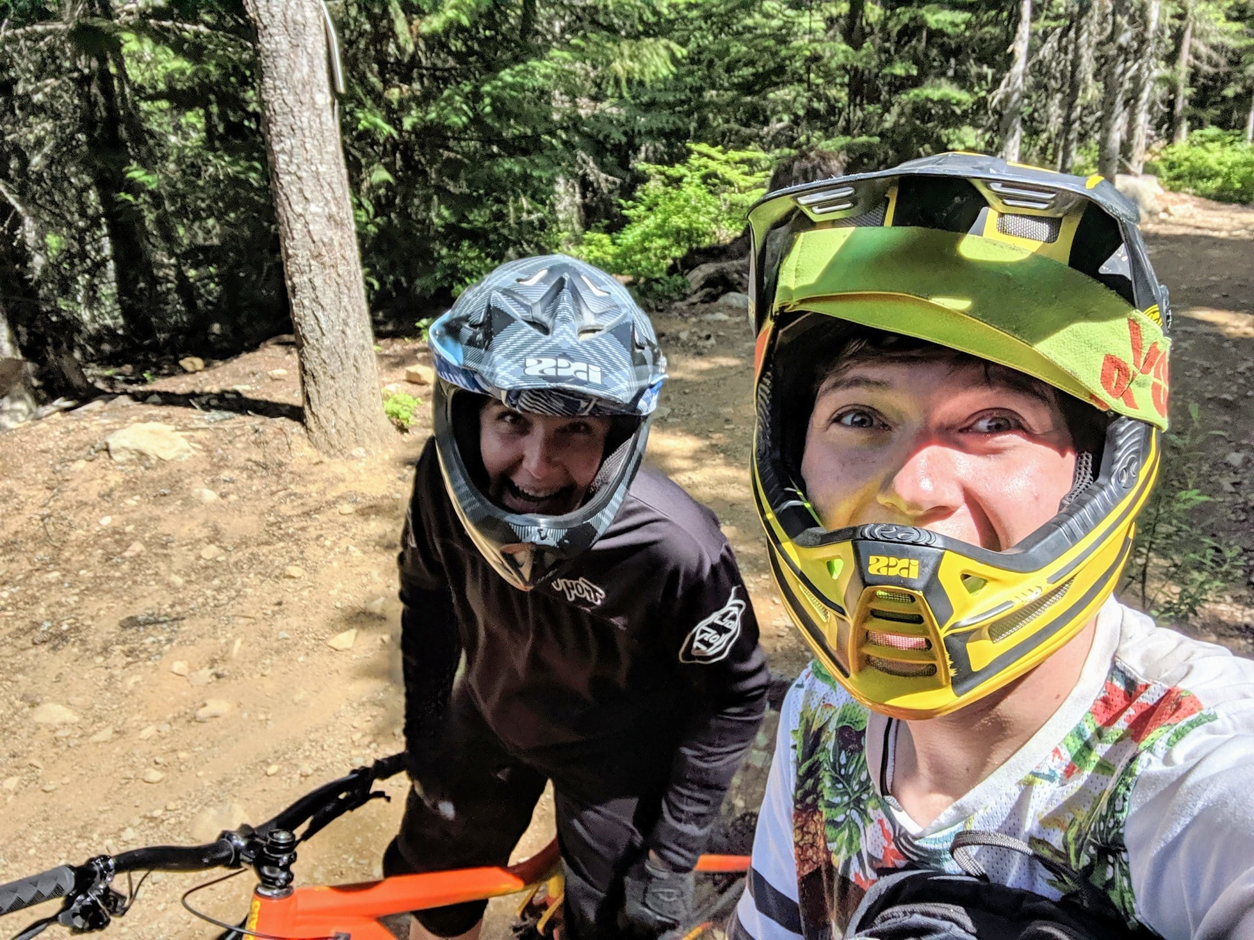 A selfie of a young man and woman riding mountain bikes in the forest