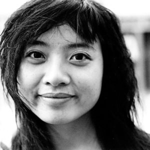 A black and white photograph of the face of a teenage girl with dark hair looking straight at the camera and smiling slightly