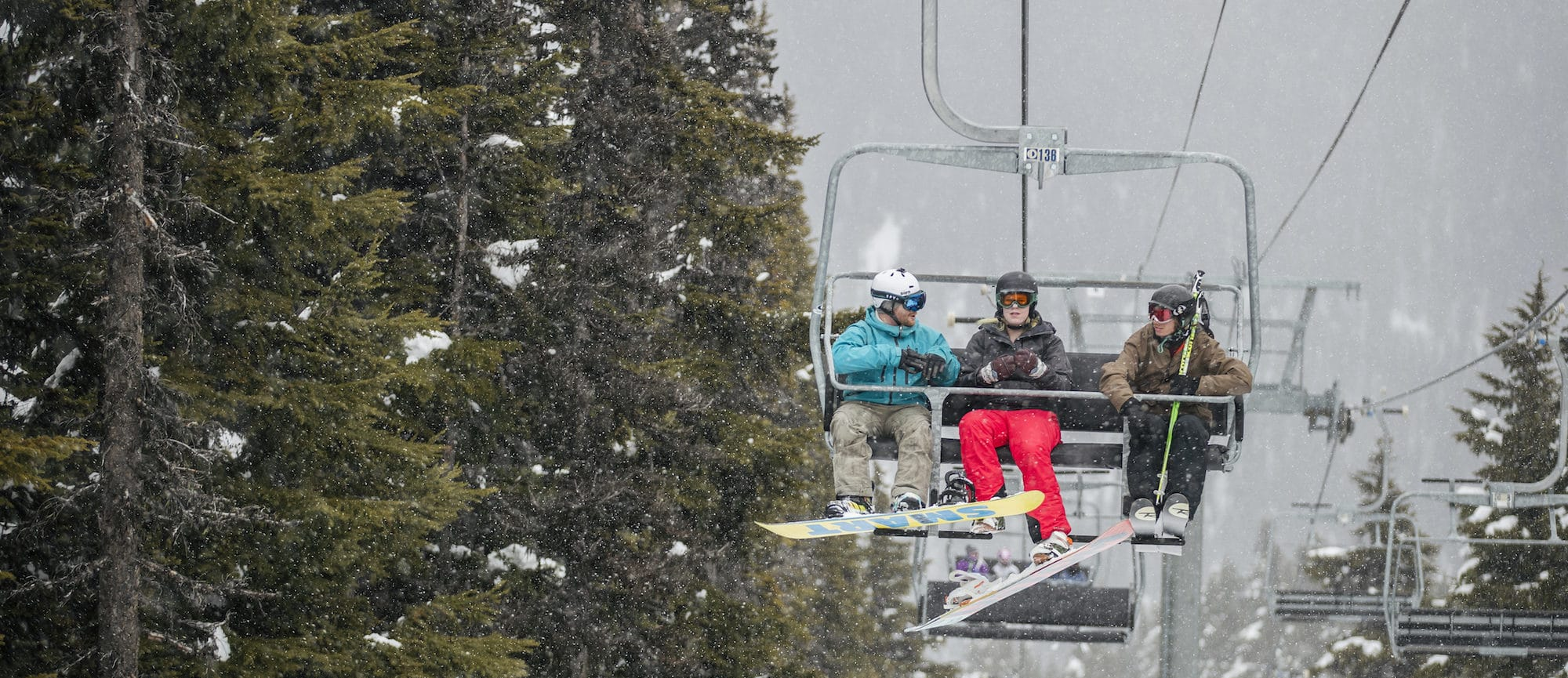 A photograph of three people riding a chairlift. It is winter and they are wearing ski and snowboard gear and talking to each other
