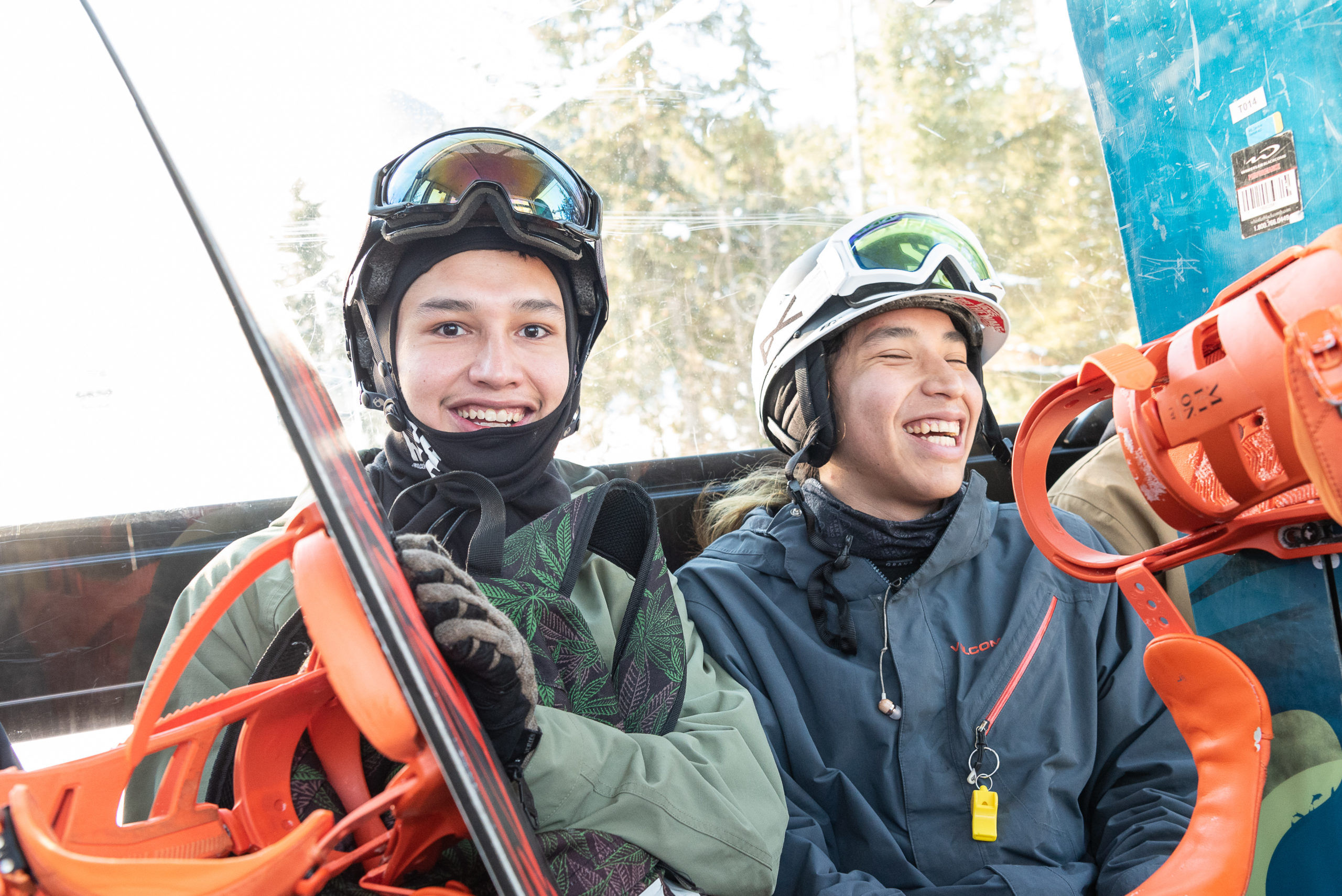 Close-up photograph of two young men in snowboard gear laughing