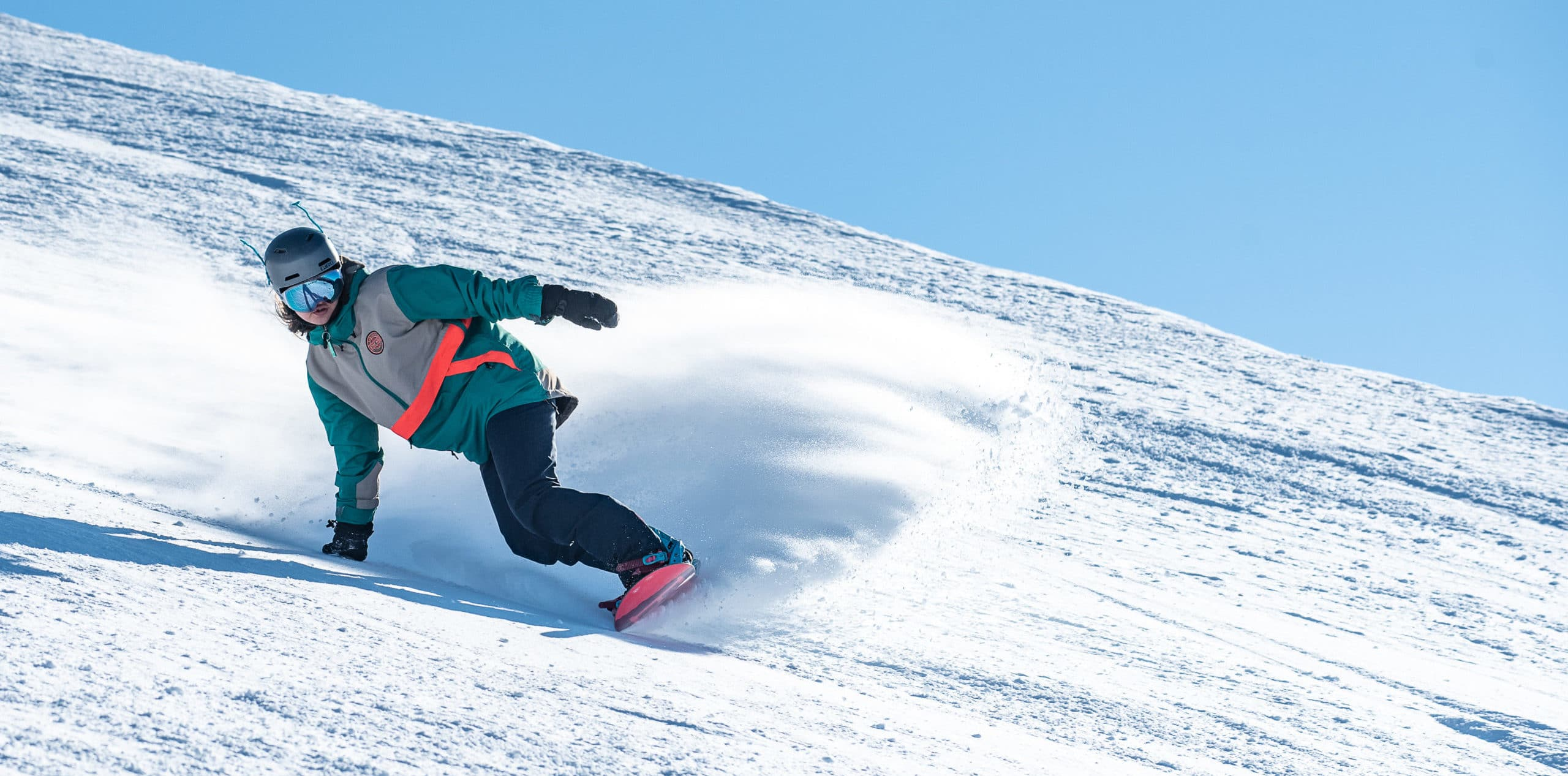 A photograph of a young woman snowboarding. The sky is blue and she is surrounded by a spray of powder snow.