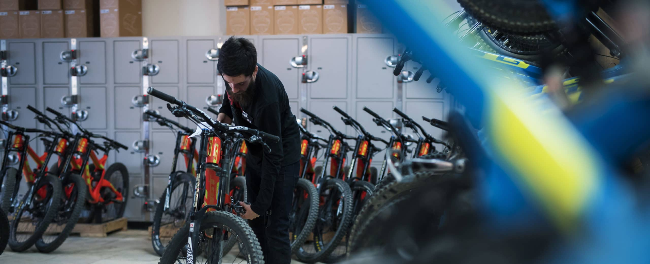 A photograph of a young man working in a bike shop. He is adjusting a mountain bike, with a row of bikes behind him.