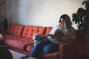 stock photo of a plus-size white woman with tattoed arms, looking comfy reading a book on the sofa with her little white dog.