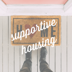 """a brown mat says """"HOME"""", with a red heart. A person's leg's with black pants and feet stand in front of it. """"Supportive Housing"""" is written in cursive script over the image."""