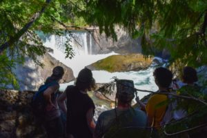 A few young people looking at a gorgeous waterfall and natural pool on one of Whistler's epic hikes. This summer we're adding hiking to our Adventure Sessions activities so we can help with social distancing.