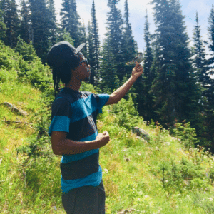 Cedric is a cool dude. This photo shows him standing on a green hillside with his arm outstretched, feeding a small bird. Let's all try to be as cool as Cedric is!