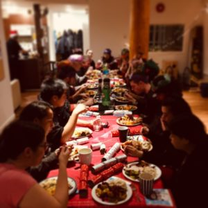 A large group of people are sharing a celebratory dinner at a Community Centre.