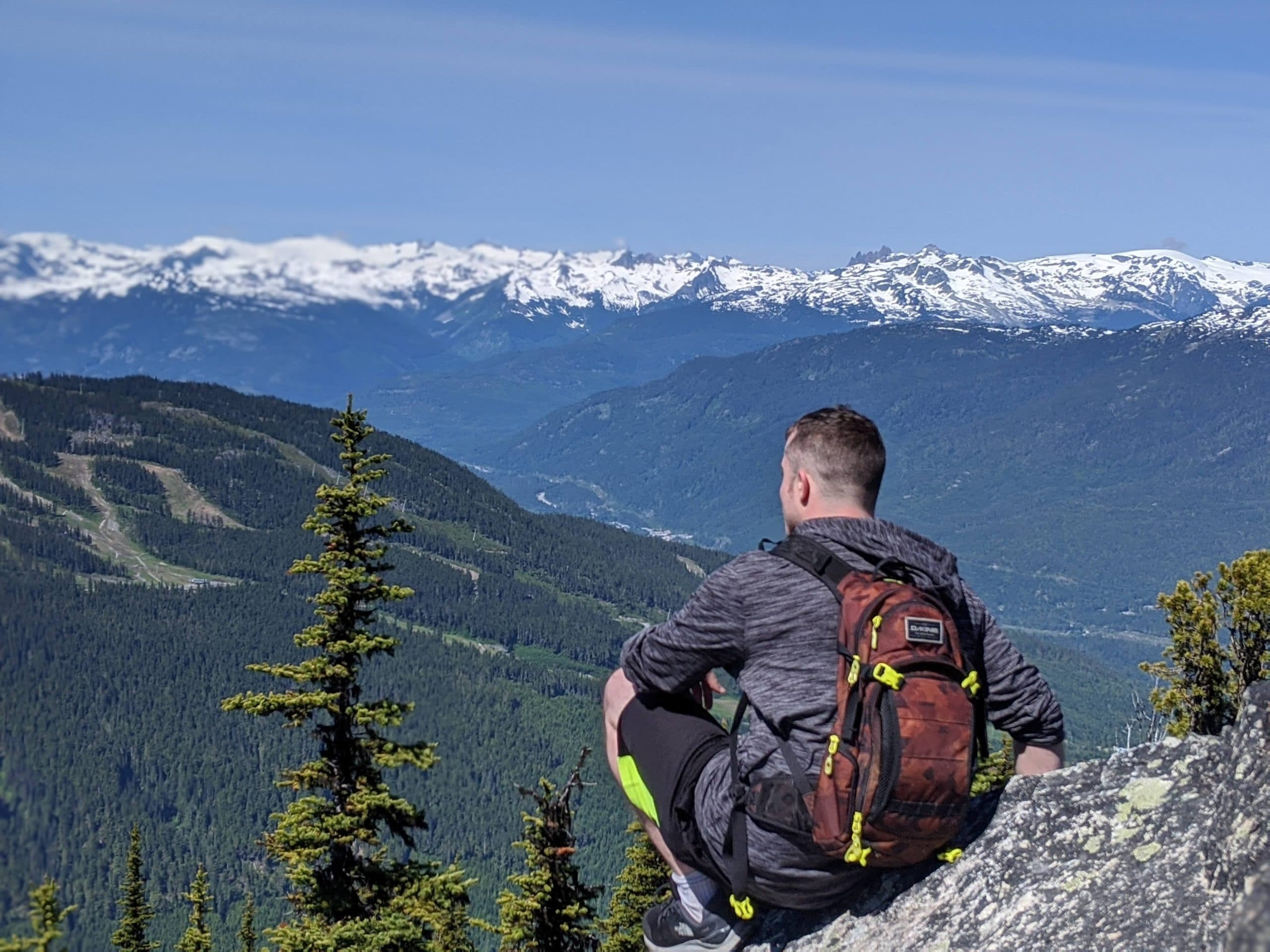A young man sits on a mountaintop with his back to the camera. He looks out over the snow-capped peaks and forests of Whistler.