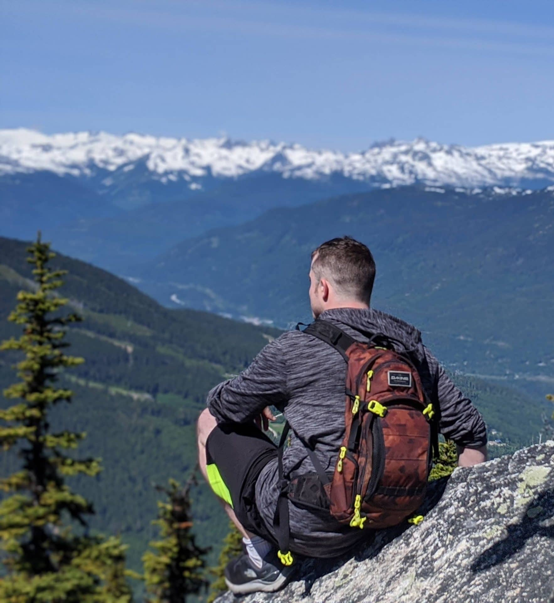 A photograph of a young man sitting on a mountain side. He has his back to the camera and is looking out over a mountain valley with snowcapped peaks in the distance and blue skies.