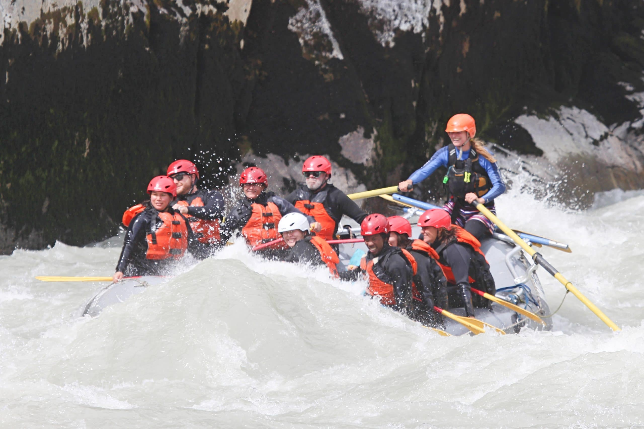 A group of young people whitewater rafting through a canyon in Squamish, BC.